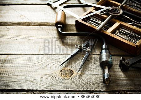 Old drill, compasses, ruler and compasses on a wooden background.