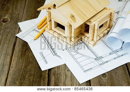 Many drawings for building and small house on old wooden background.