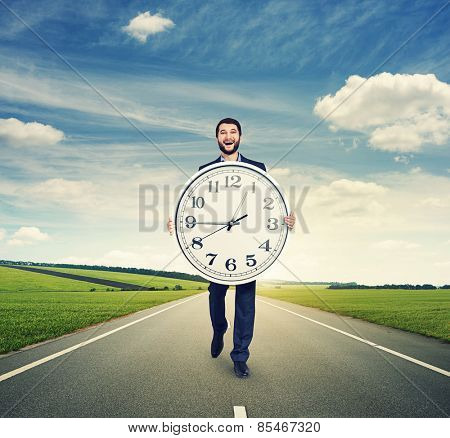 laughing man walking on the road and holding big white clock