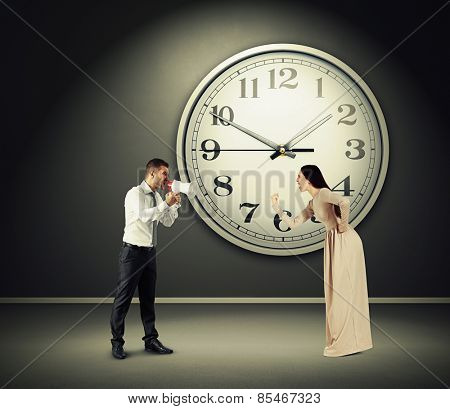 angry yelling woman and screaming man with megaphone in dark room with big clock on the wall