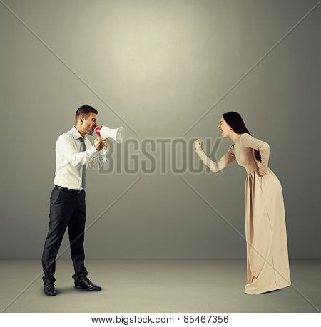 angry yelling woman showing fist to emotional man with megaphone. photo over dark background