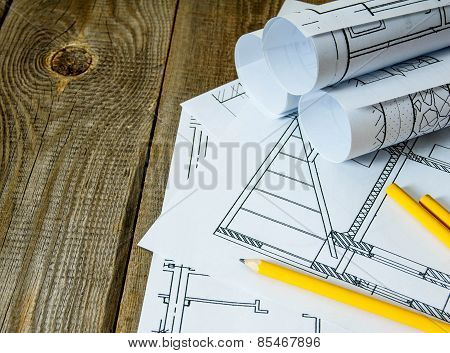 Many drawings for building and pencils on old wooden background.