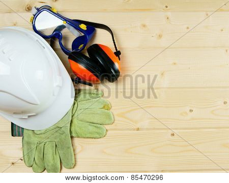 helmet, gloves and ear-phones on a wooden background.