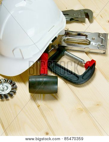 helmet, clamp, stapler and other tools on wooden background.