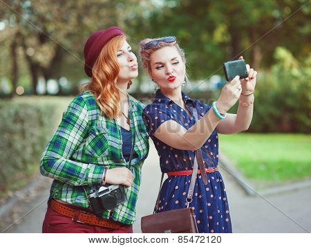 Two Beautiful Hipster Girls Taking Pictures Of Themselves On Mobile Phone