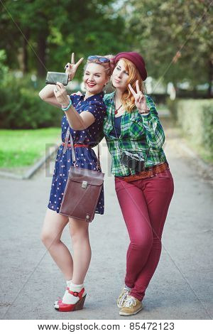 Two Hipster Girls With Braces Taking Pictures Of Themselves On Mobile Phone