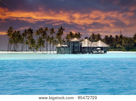 Island in ocean overwater villas at the time sunset