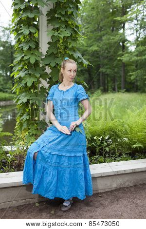 The young beautiful woman in a blue dress in the arbor twined a green bindweed
