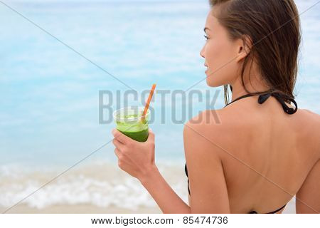 Green vegetable smoothie - woman drinking detox vegetables smoothie in bikini after swimming in ocean sea on beach. Fitness healthy lifestyle concept with beautiful multiracial Asian Caucasian model