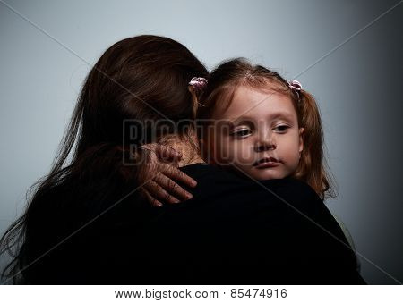 Small Sad Daughter Hugging Her Mother With Love On Dark