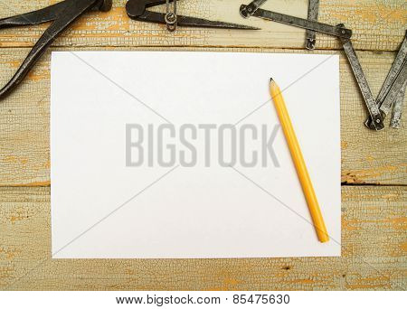 Paper with pencil and the vintage working tools on wooden background.