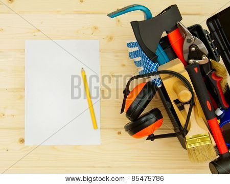 Sheet of paper with pencil and tools in box on wooden background.