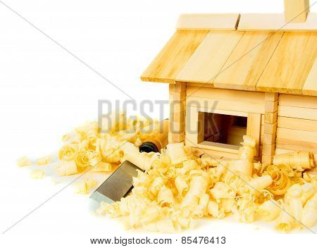 House construction. Joiner's works. The small wooden house, chisel, plane and shaving on white backg