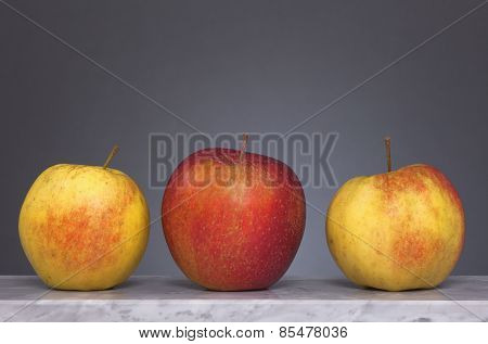 Three  Apples In Front Of Gray Background