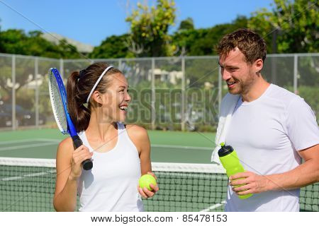 Tennis sport - couple relaxing after playing game of tennis outside in summer. Happy smiling friends on outdoor tennis court living healthy active fitness lifestyle. Woman and man athletes.
