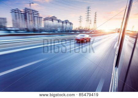 Car driving on freeway at sunset, motion blur