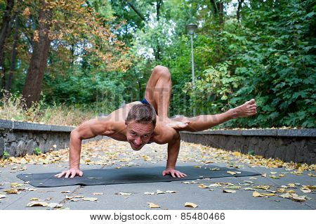 Handsome Smiling Flexible Athletic Man Doing Yoga Asanas In The Park