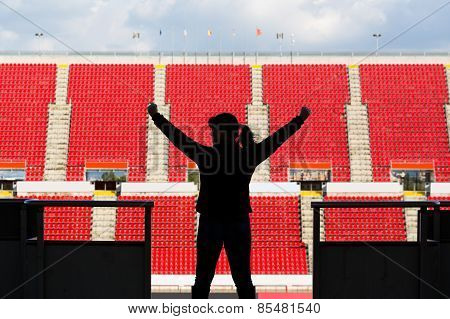 female football fan from behind in a empty stadium