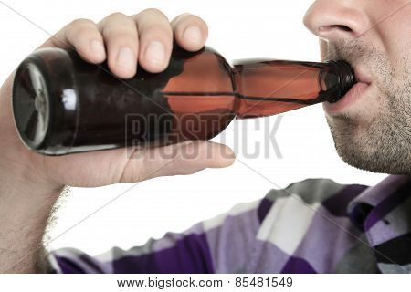 Casual young man holding bottle of beer, smiling. Isolated on wh