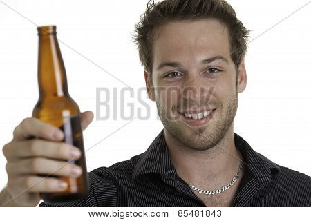 Casual young man holding bottle of beer, smiling. Isolated on white.