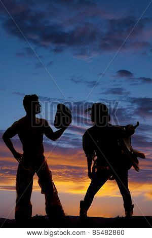 Silhouette Of Cowgirl Holding Saddle On Shoulder Look At Cowboy