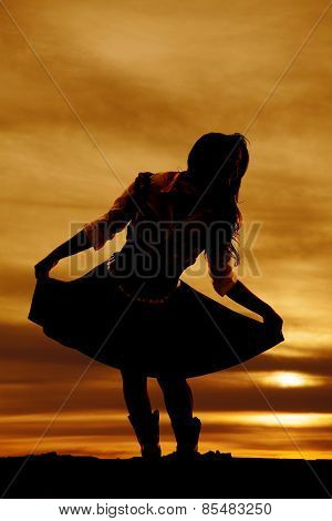 Silhouette Of Woman Holding Out Her Skirt Leaning Over