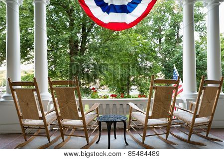 Four Wooden Rocking Chairs And The American Flag