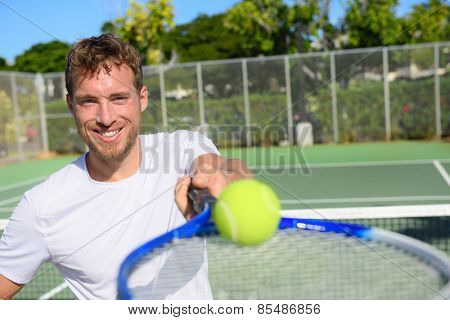 Tennis player portrait man showing ball and racket. Smiling happy male athlete inviting you to play tennis. Healthy active sport and fitness lifestyle concept.