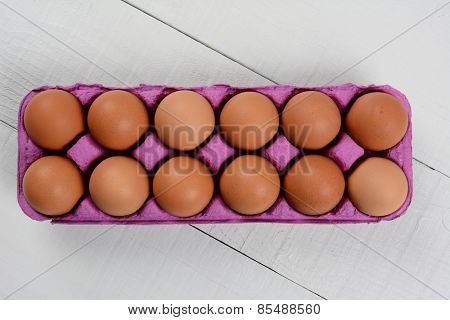 High angle shot of a dozen organic brown eggs in a pink cardboard carton on a rustic white wood table. Horizontal format with copy space.