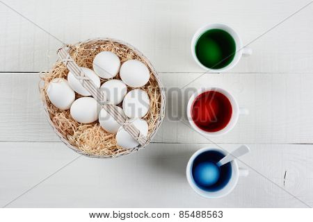 High angle shot of a basket full of eggs to be dyed for Easter. Three cups of dye with eggs soaking are next to the baskets of un-dyed eggs on a white wood kitchen table.