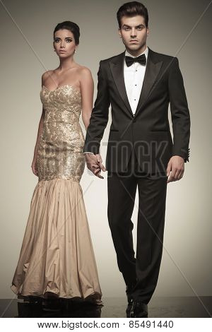 Attractive elegant man walking on studio background while holding his lover hand.
