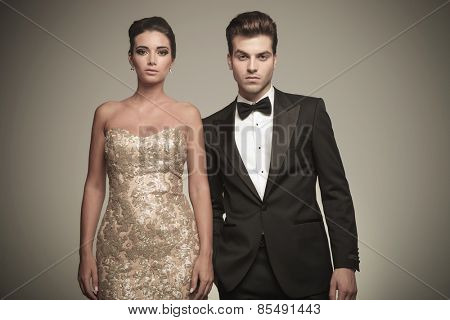 Portrait of a elegant young couple posing on studio background, both looking at the camera.
