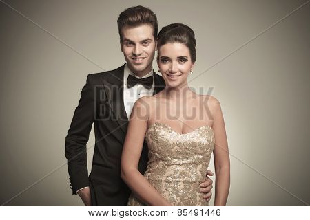 Portrait of a happy young elegant couple posing together on gery studio background.