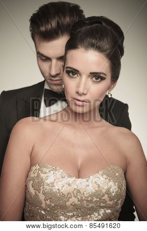 Close up picture of a beautiful woman posing together with her husband. He is standing behind her.