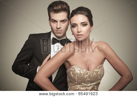 Close p picture of a elegant couple posing on studio background, both looking at the camera.
