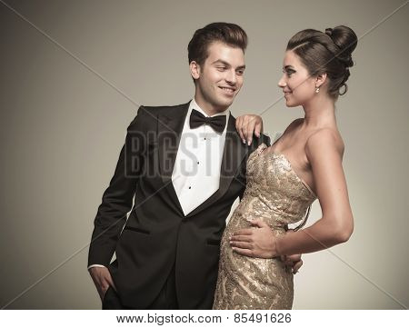 Smiling young handsome man looking at his wife while embracing her.