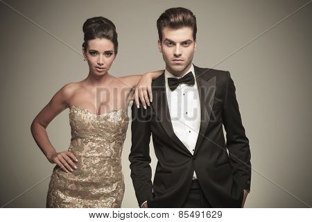 Beautiful elegant woman leaning on her lover while both look at the camera.