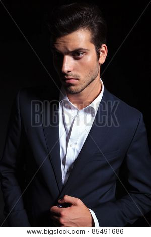 Close up portrait of a handsome young business man unbuttoning his jacket while looking away from the camera.