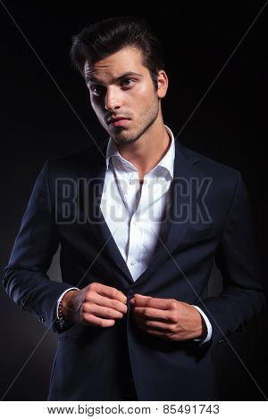 Portrait of a young handsome business man looking up while closing his jacket.