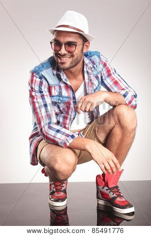 Picture of a smiling young fashion man, stiing while looking away from the camera.