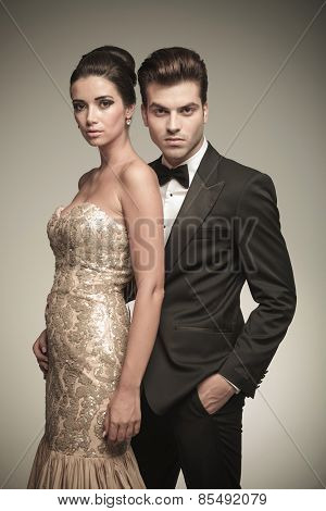Attractive elegant man holding his lover while looking at the camera.
