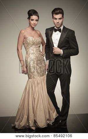 Young elegant man and woman posing next to each other on grey studio background.