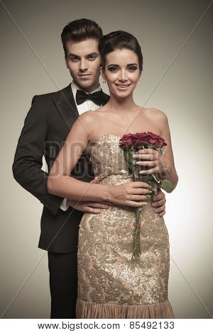 Elegant man holding his wife from the back while she is holding a bunch of red roses in her hands.