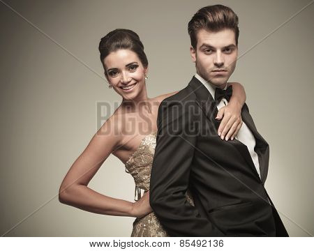 Happy young elegant woman embracing her husband from the back. Both looking at the camera.