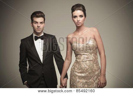 Elegant fashion couple holding hands while posing on grey studio backrground.