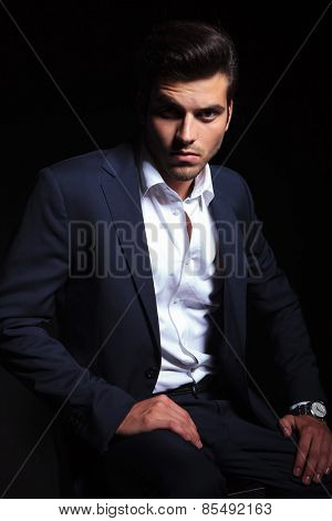 Handsome young business man sitting on a chair while resting his hand on his leg.