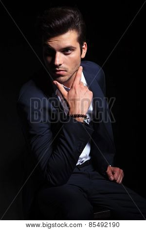 Elegant business man posing on black studio background while sitting on a chair holding two fingers to his chin.