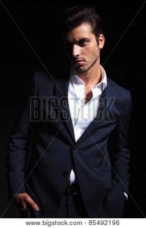 Young elegant business man looking away from the camera while holding both hands in his pocket, on black background.