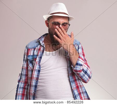 Young fashion man holding his hand to his mouth while yawning.