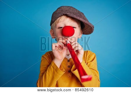 Little boy blowing a party horn blower